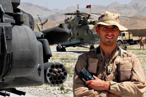 Roy de Ruiter naast een Apache-gevechtshelikopter in Afghanistan.